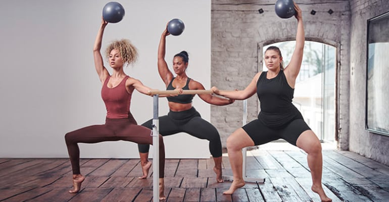 women doing wide squats while holding a medicine ball overhead