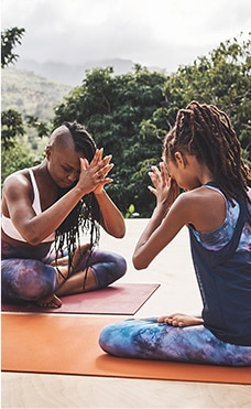two women wearing athleta top and bottoms doing yoga