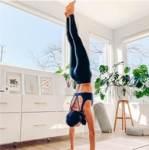 woman wearing athleta top and bottoms doing a hand stand