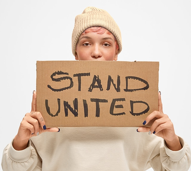 Person posing with a cardboard sign that says Stand United