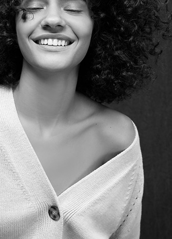 Black and white photo of a smiling woman wearing a blouse