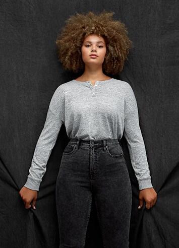 Woman wearing jeans and a henley sweatshirt