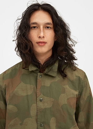 Person wearing collared shirt with a camouflage pattern