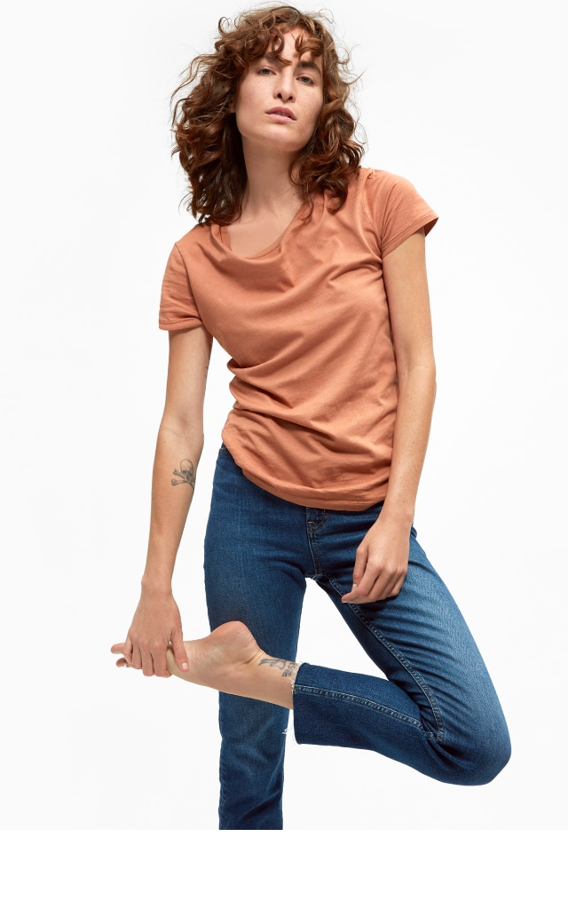 Woman in an orange tee shirt and jeans