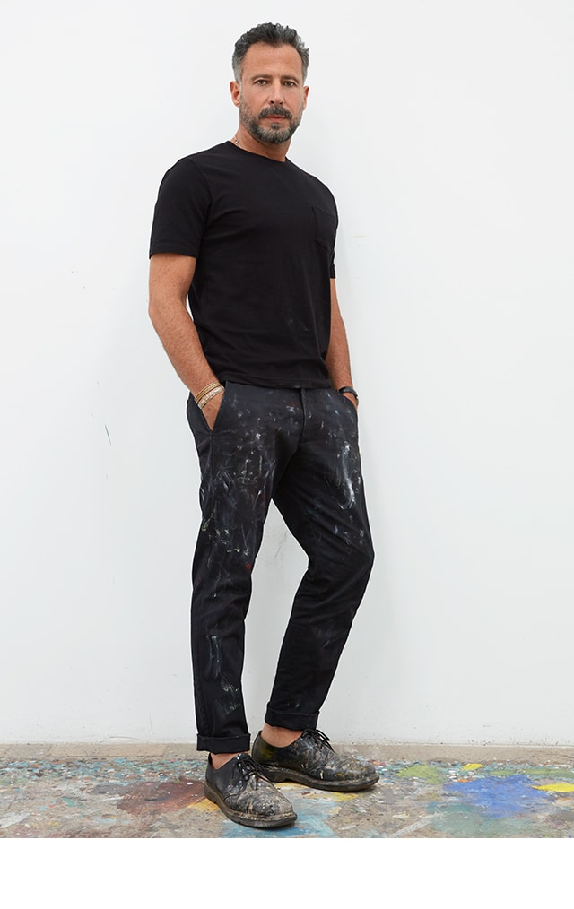 Man wearing a black tee shirt and dark jeans